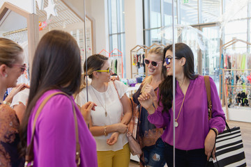Women trying on sunglasses at boutique.