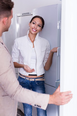 Seller offers to a woman help to buy fridge