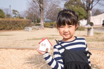 家の模型を持つ女の子
