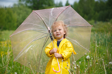 A little child in a yellow raincoat under an umbrella on a summer day.