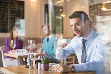Man drinking tea in restaurant.