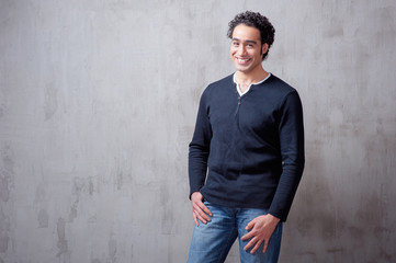 Charming and self-confident. Handsome young arabic man holding hand in pockets and looking at camera while standing against grey background