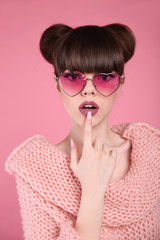 Beauty wow. Fashion surprise teen girl model. Brunette in heart sunglasses with matte lips and hairstyle posing over studio pink background.