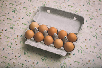 top view of brown chicken eggs in their cardboard, on vintage floral background