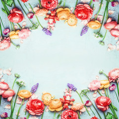 Floral Frame of lovely colorful flowers on blue turquoise shabby chic background, top view, horizontal