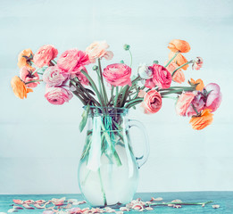 Lovely bouquet of beautiful  Ranunculus  flowers in glass vase on table at light blue turquoise background, pastel color