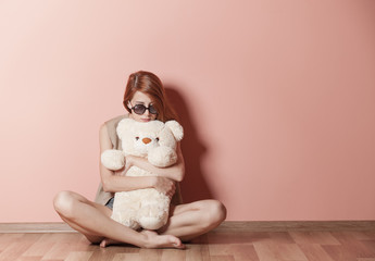 photo of beautiful young woman hugging teddy bear and sitting near the wall