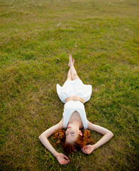 photo of beautiful young woman lying in the field and relaxing