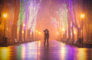 photo of cute couple kissing on the wondeful night park background