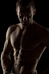 silhouette of half-naked handsome and muscular young man posing on a dark background