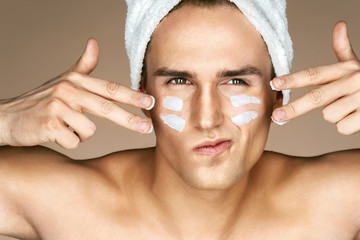 Young man with moisturizer cream on the face. Photo of man with perfect skin. Beauty & Skin care concept