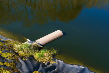 Pipe from underground ending in a leachate pond. Location Ronneby, Sweden.