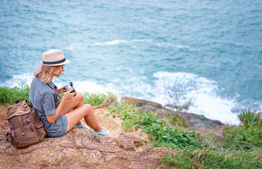 Photography and travel. Young woman in hat with rucksack holding camera sitting on cliff with sea view.