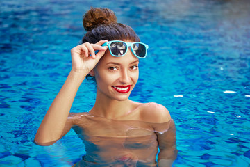 Relaxation and leisure. Beautiful young woman enjoying suntan in resort swimming pool.