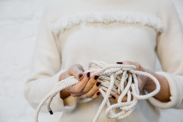 Hands holding white yarns
