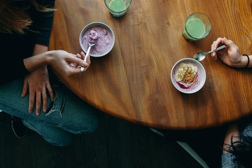 Breakfast table top with hands, smoothie bowls and matcha