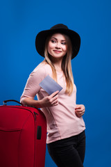 Beautiful young girl with a suitcase and a ticket on a blue background