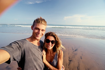 Pretty young loving couple taking selfie together on smartphone on beach.