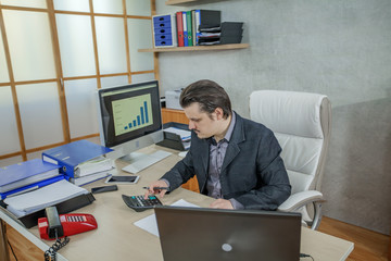 A young businessman is calculating something in his office. He is very focused.