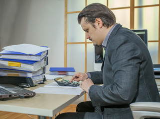 A young businessman is calculating something and writing it down on a piece of paper.