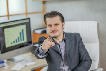 A businessman is pointing at someone. He is sitting in his office.