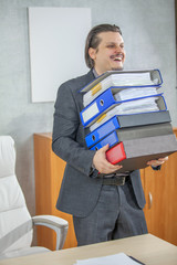 A businessman is carrying many folders in his hands. He is feeling happy.