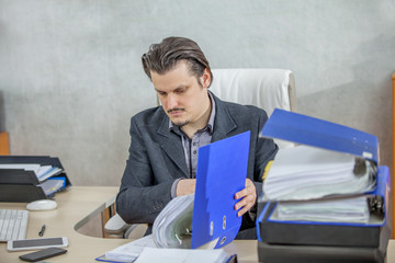 A businessman is checking the files and documents in the folder and he looks very focused.