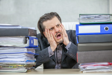 A young businessman is shocked and worried about all the paperwork in front of him.