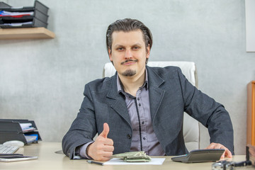 A businessman sitting in his chair is giving a thumbs up.