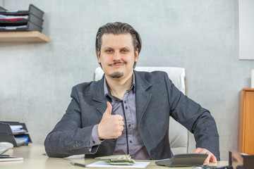 A happy businessman gives a thumbs up and looks happy in his office.