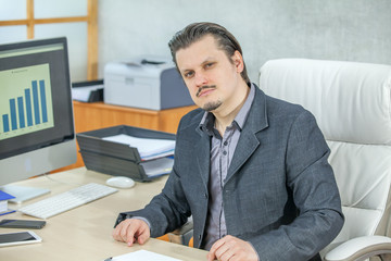 A serious businessman is looking into the camera. He is working in his office.