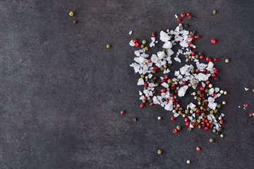 Black food background with spices. A mixture of peppers and salt on shale stone. Top view.