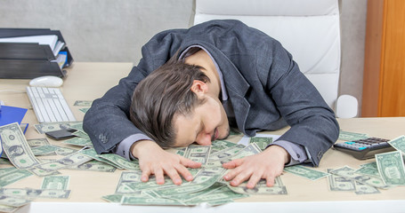 A young accountant is sleeping on the money which is on a table in the office. Many American dollars are on a table.
