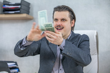 A young businessman is happily calculating the money in his hands.