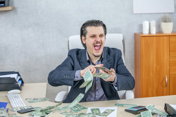A happy businessman is having lots of money on the table. He is giving an expression of excitement.