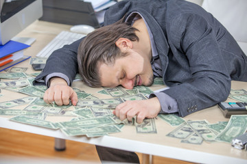 A businessman is hugging all the money on the table in front of him. He is happy.