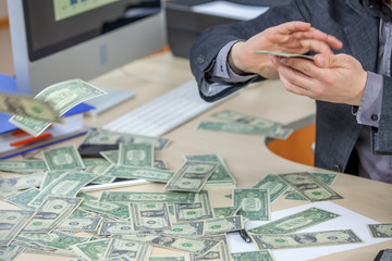 Money is spread out on a table in a businessman's office. He is counting it.