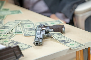 Money and a gun are together on a table. Money is spread out across the table in an office.