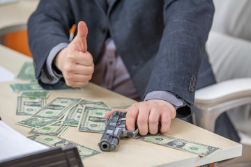 A businessman is having one hand on a gun and with the other he is giving thumbs up.