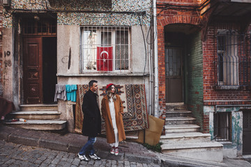 Couple standing on the background of old carpet. Old streets of Istanbul