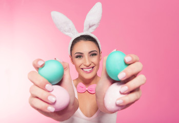 Smiling bunny woman showing a easter  eggs