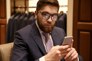 Concentrated young bearded businessman sitting indoors chatting