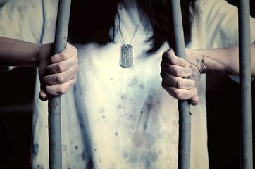 Donna che piega le sbarre di una prigione. Immagine astratta utilizzabile per concetti come evasione, diritti delle donne, disuguaglianza, rivincita, libertà.