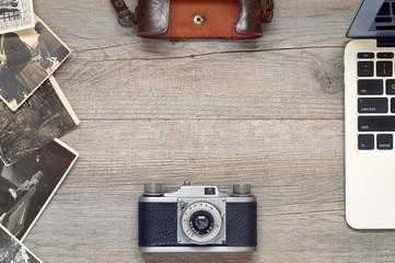 Vecchia macchina fotografica con fotografie cartacee e computer su tavolo di legno rustico. Progresso della fotografia da analogico a digitale