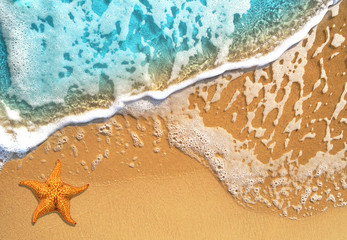 Beautiful blue wave on a sea beach with a starfish. Background template for summer holidays and tropical travel.