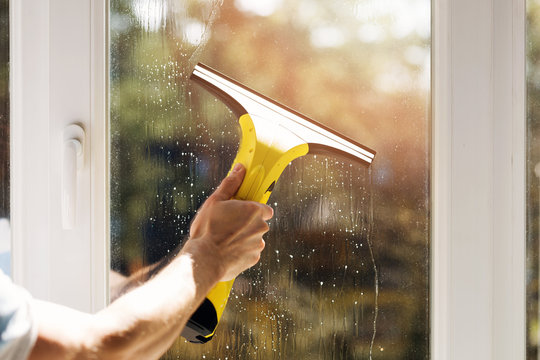 hand cleaning window with vacuum cleaner