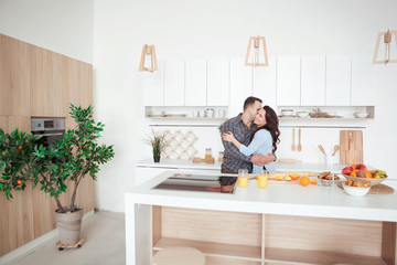 Happy couple hugging in the white loft stile kitchen