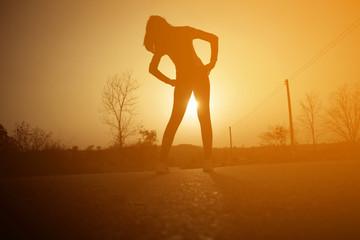 Woman exercising outdoor at sunset Wall mural