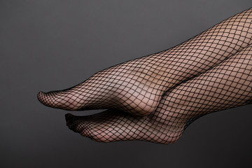 Woman feet with fishnet tights