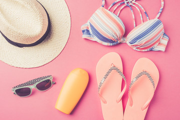 Summer background with straw hat, flip flops, swimsuit and sunglasses. Top view